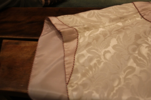 Unusual design details on the chasuble feature a turn back cuff on edge of chasuble shoulder seam